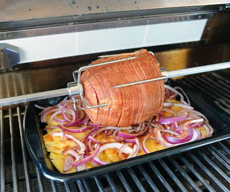 spiral ham on rotisserie over pan of pineapple and onion