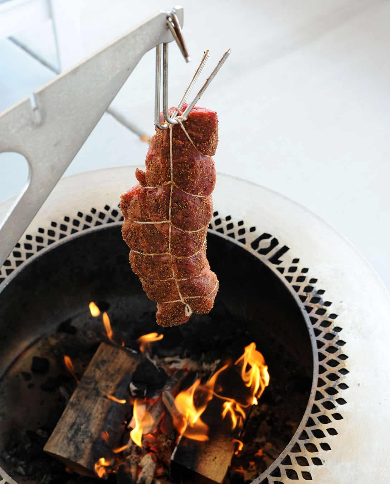 beef roast hanging over fire