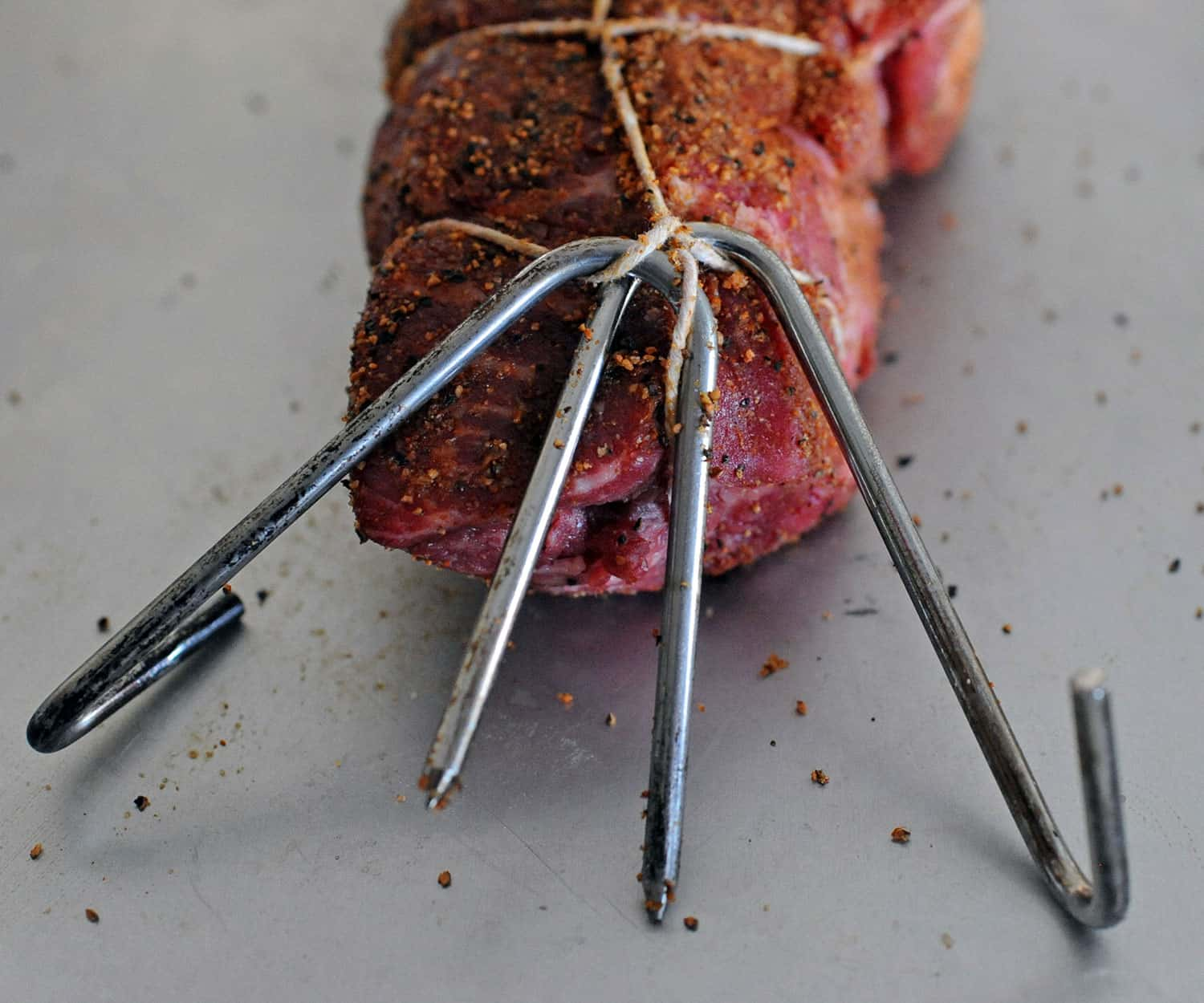 metal meat hooks in twine wrapped around beef