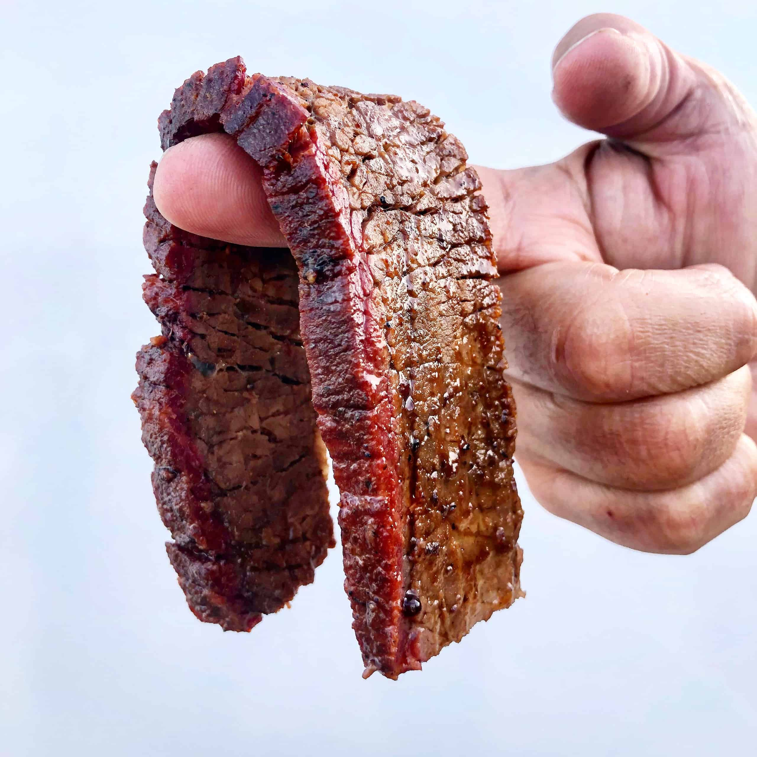 thick slice of smoked brisket draped over finger