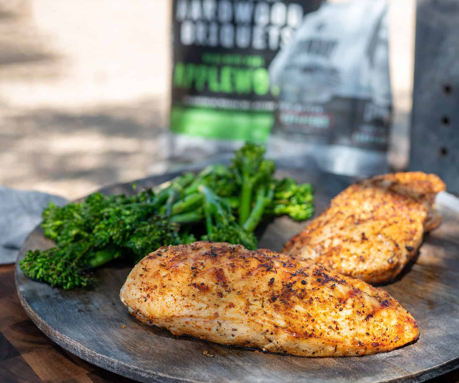 plate of two chicken breasts and broccoli by bag of Cowboy Charcoal