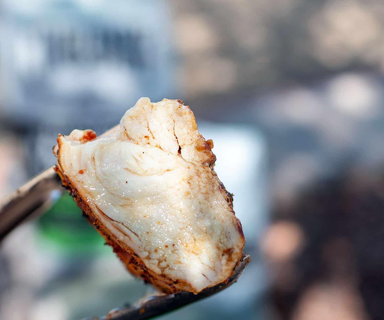 juicy chicken breast held with tongs