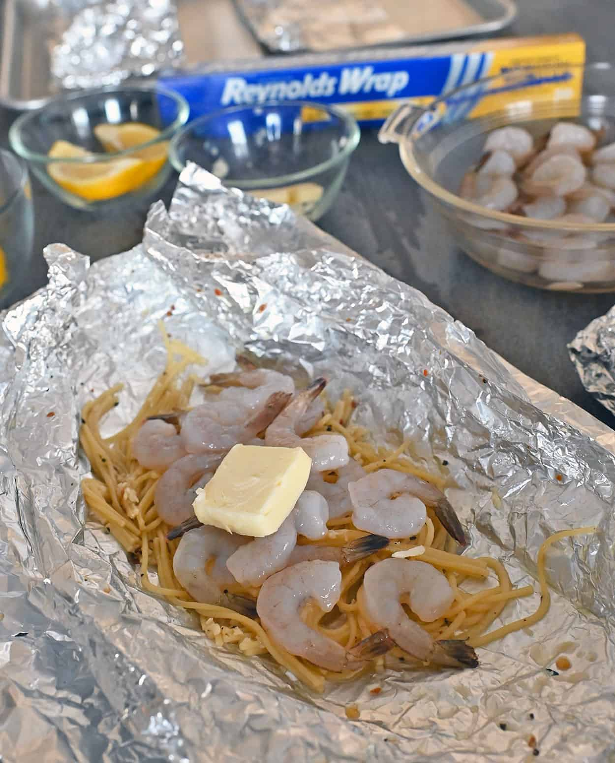 open foil packet with cooked noodles, raw shrimp and butter